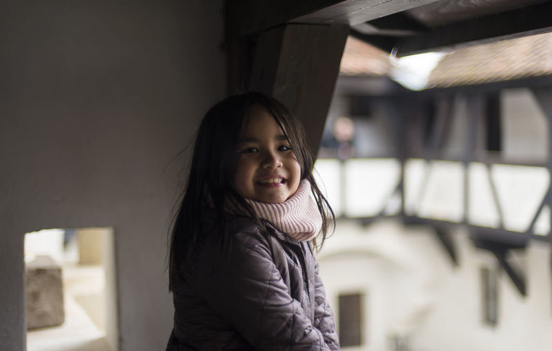 Portrait of cute girl standing at balcony