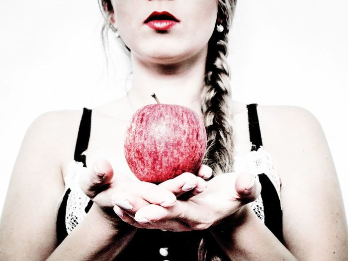 Midsection Of Woman Holding Apple Against White Background
