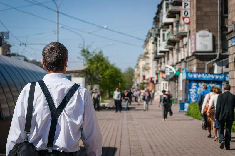 Rear view of man walking on sidewalk in city