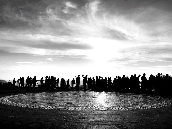Silhouette people on shore against sky