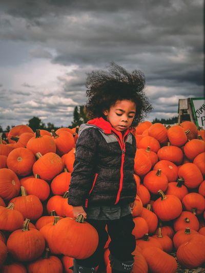 Full length of girl standing against orange sky