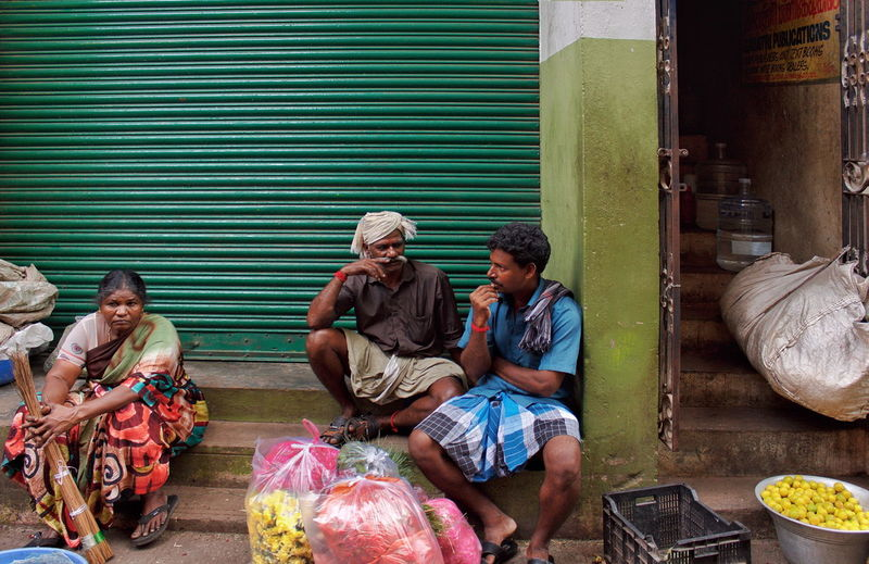 Rear view of people sitting at market stall