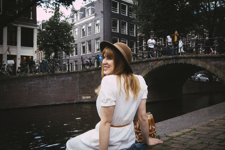 Young woman smiling while standing at canal
