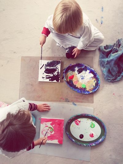 High Angle View Of Siblings Painting On Papers At Home