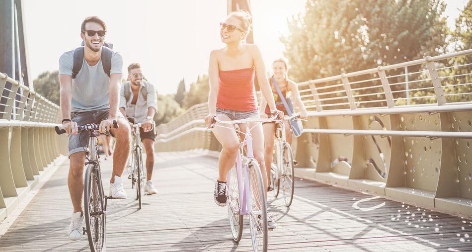 Friends Riding Bicycles On Bridge