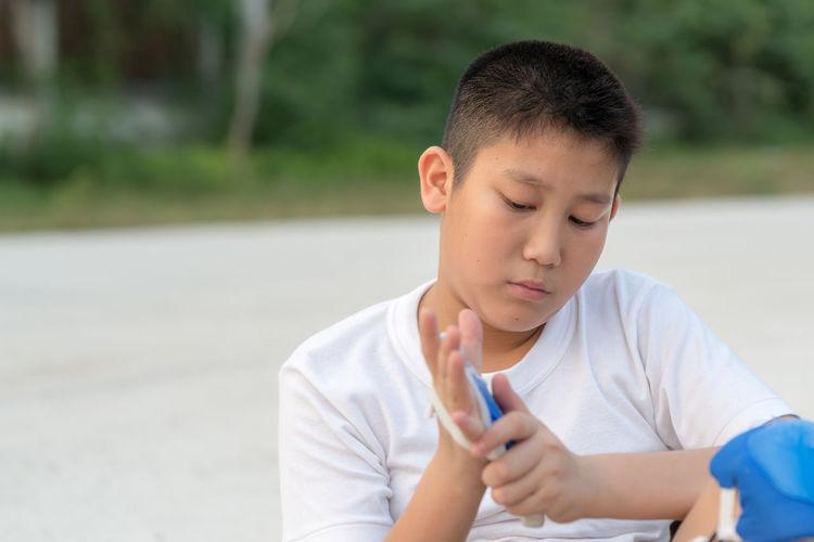 Boy wearing inline skating glove on road