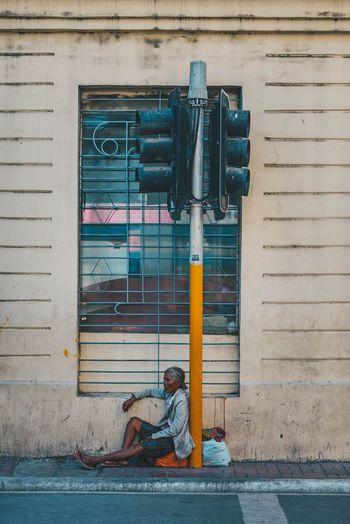 Man sitting on closed door of building