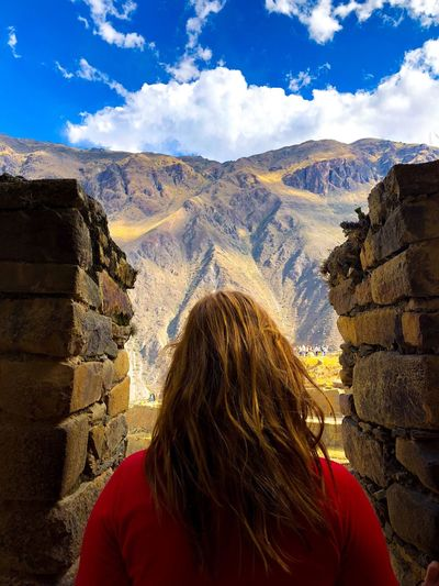 Rear View Of Woman Looking At Mountain While Standing By Brick Wall