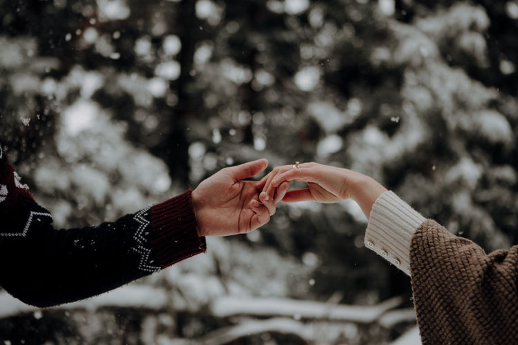 Cropped image of couple holding hands in forest during winter