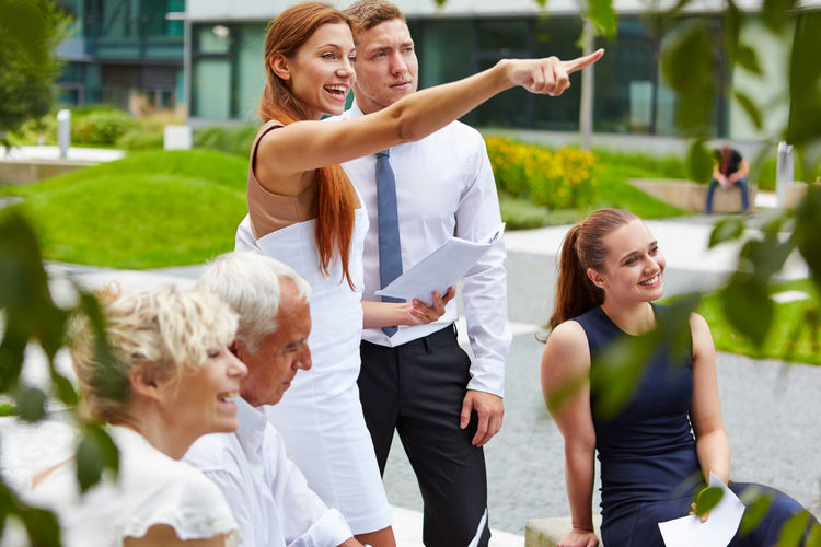 Businesswoman pointing while standing by colleagues outdoors