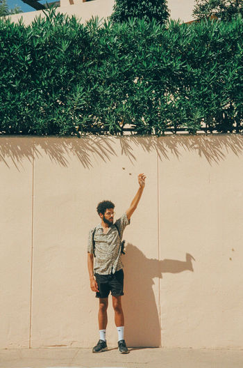 Full length of boy with arms raised against wall