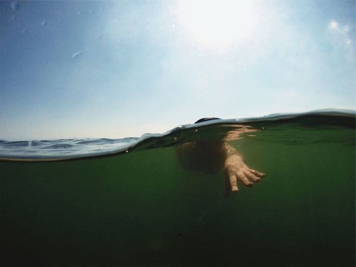 Person Swimming In Sea Against Clear Sky