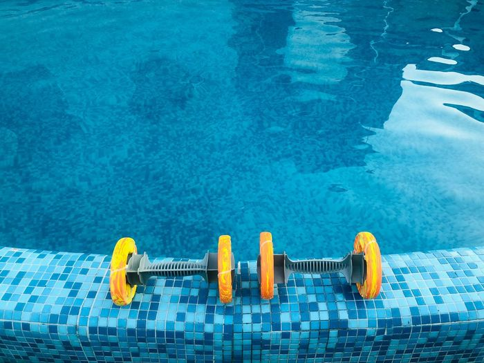 High angle view of dumbbells on swimming pool
