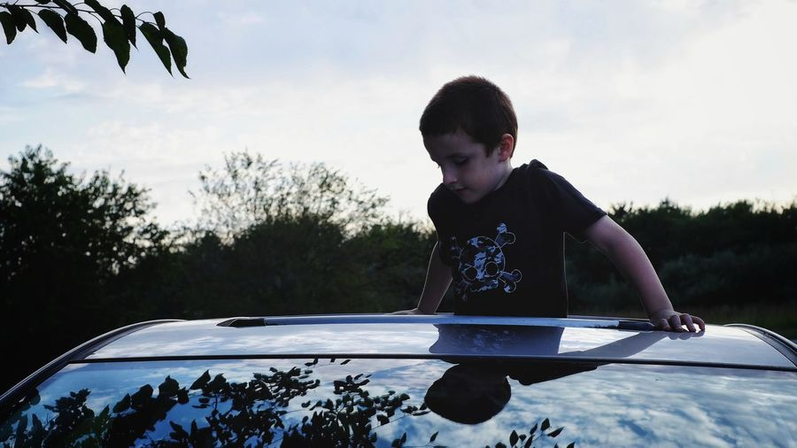 Boy standing and looking through car roof against sky