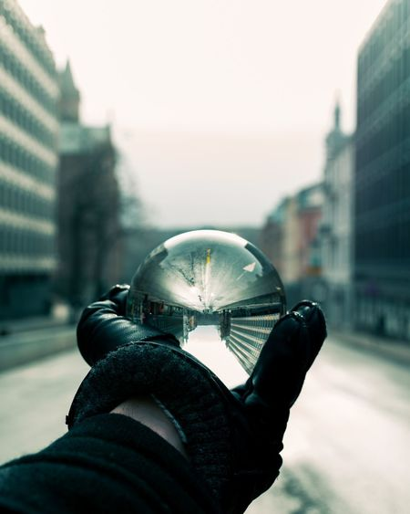 Close-up of hand holding crystal ball against city buildings