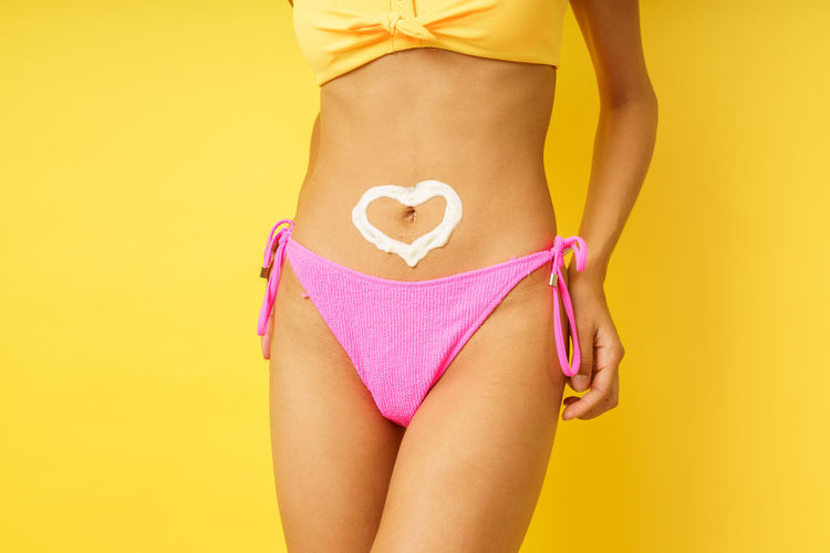 Midsection of woman with pink hair standing against yellow background