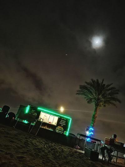 Illuminated lights on beach against sky at night