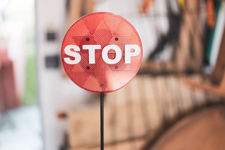 close-up of road sign on footpath Built Structure Circle Close-up Communication Day Februar Focus On Foreground Footpath Geometric Shape Information Information Sign No People Outdoors Red Road Sign Selective Focus Shape Sign Text Warning Sign