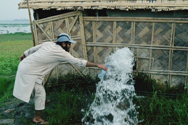 Man Filling Bottle From Splashing Fountain