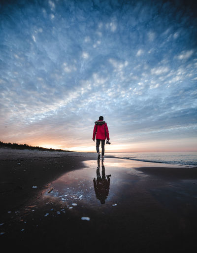 Rear view of woman on bicycle at beach during sunset