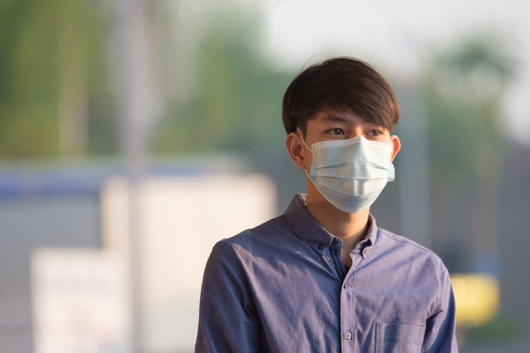 Teenage boy wearing mask standing outdoors