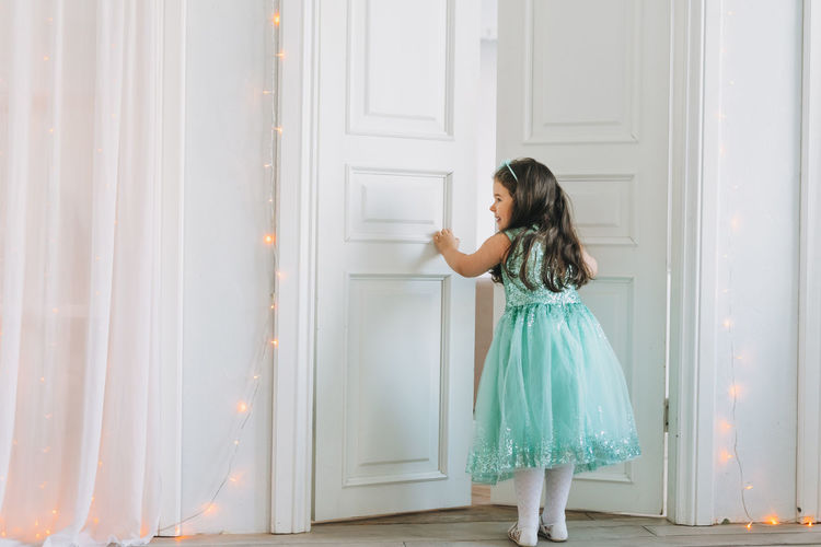 Cute happy little girl in mint fancy dress open door at bright room, birthday, christmas time