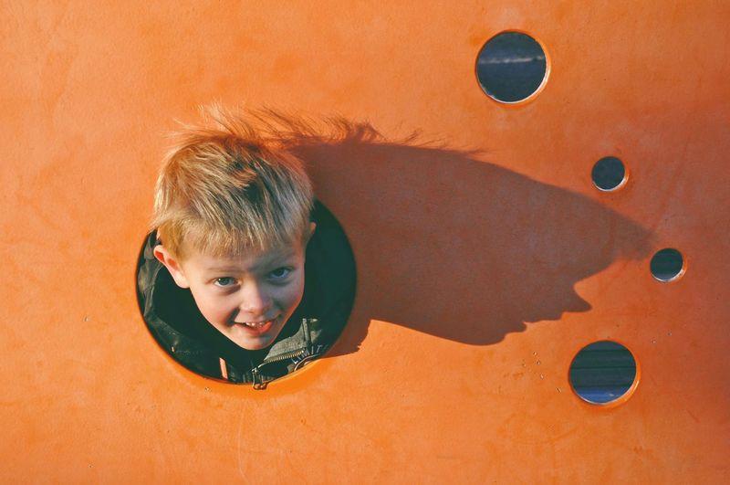 Portrait of cute boy playing against wall