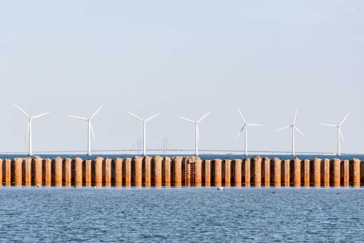 Windmills By Groyne In Sea Against Clear Sky