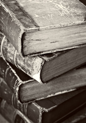 Sepia toned image of a stack of old worn books.