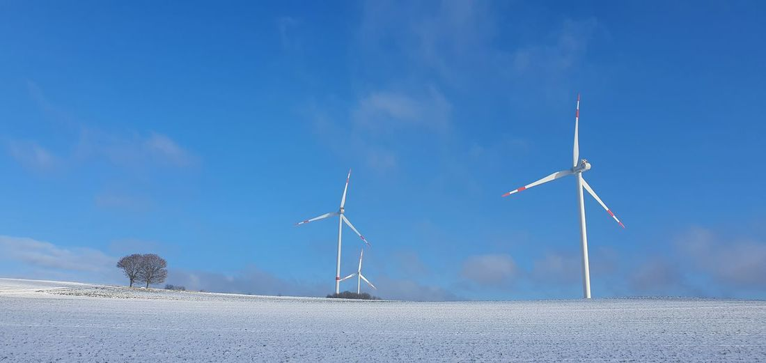 Wind turbines on land against blue sky