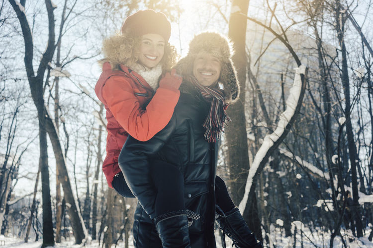 Portrait of man piggybacking girlfriend in forest during winter