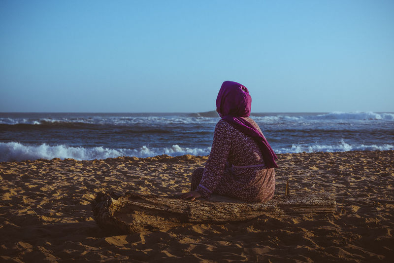 Day dreaming Sea Water Land Beach Sky Real People Rear View Horizon Over Water Beauty In Nature Leisure Activity Lifestyles Scenics - Nature Women Sitting Nature Non-urban Scene Outdoors Warm Clothing Looking At View Dreaming Pink Scarf Veil Middle Eastern Woman Muslim Woman No Face