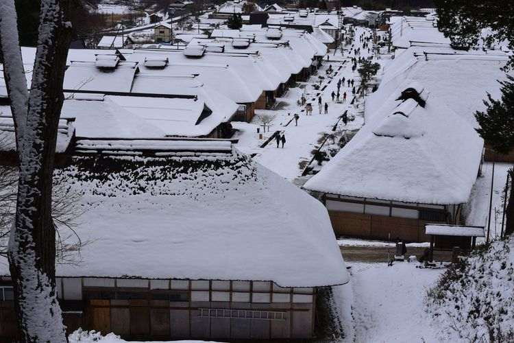 High angle view of snow covered houses on field during winter