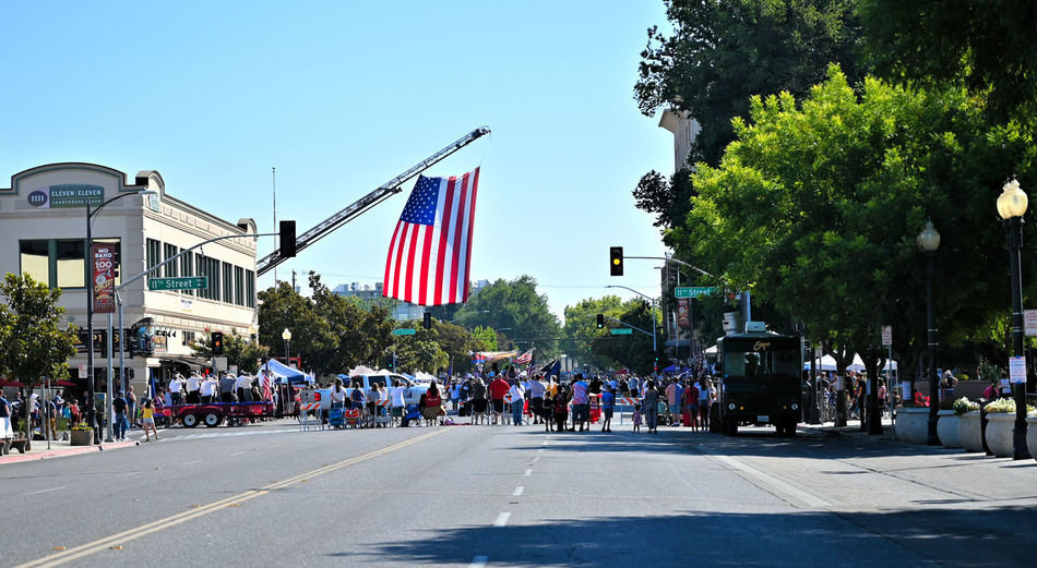 Saluting the Flag American flag while singing the national Anthem in the heart of downtown Modesto, California during the Independence Day. Street Crowd Group Of People City Architecture Flag Large Group Of People Built Structure Building Exterior Transportation Patriotism Road Real People Day Sky Plant Nature Tree City Street Outdoors Independence 4th Independence Day Streetphotography