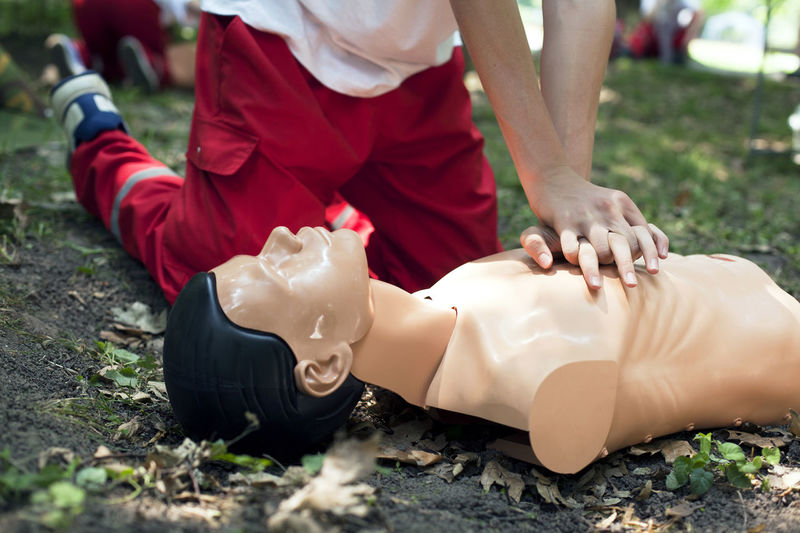 Low section of man practicing cpr dummy on field