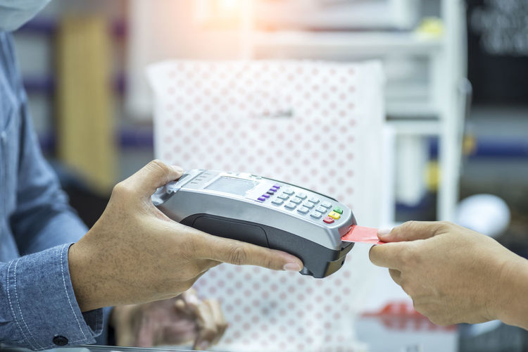 Cropped Hand Paying Bill Through Credit Card At Store