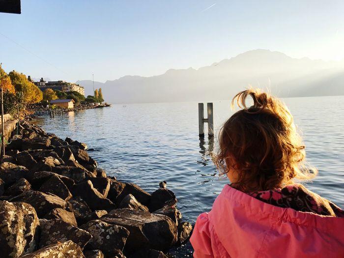 Rear view of girl by rocks in lake geneva