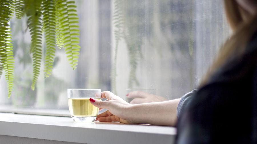 Woman drinking tea from glass window