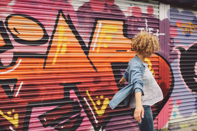 Young Woman Dancing Against Graffiti Shutter