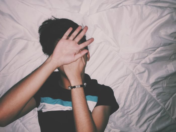 Directly above shot of person covering face while lying on bed