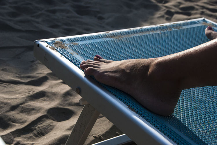 Low section of woman relaxing on deck chair at beach