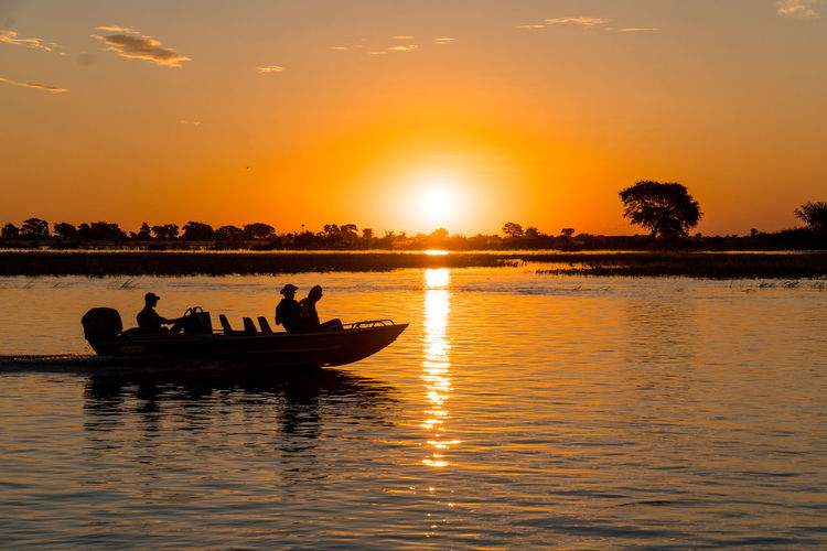 Silhouette Of People On Boat Watching Sunset