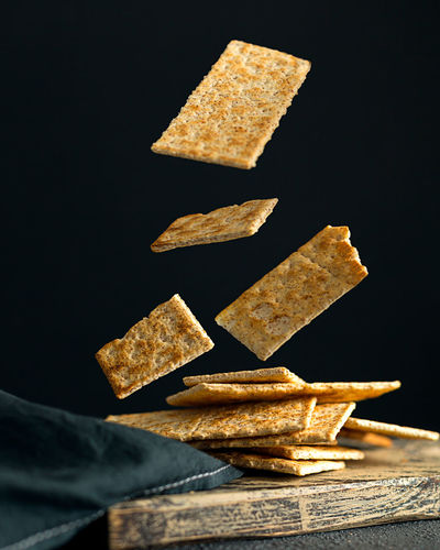 Close-up of bread on table against black background