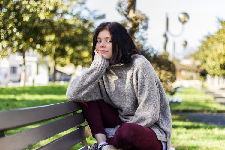 Beautiful Woman Day Focus On Foreground Front View Leisure Activity Lifestyles Looking At Camera Nature One Person Outdoors Park - Man Made Space People Portrait Real People Relaxation Scarf Sitting Smiling Tree Warm Clothing Young Adult Young Women