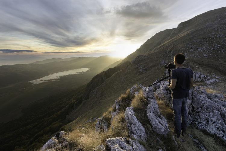 Rear view of man photographing while standing on rock against mountain and sky