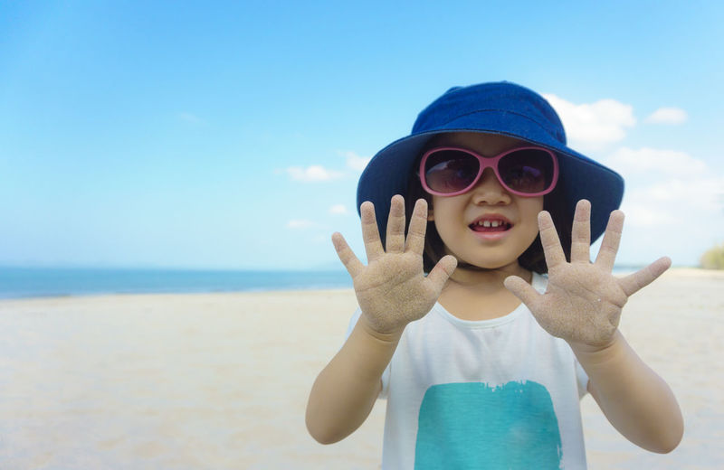 Portrait of young girl wearing sunglasses and hat against clear blue sky