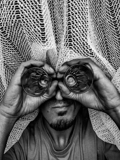 Close-up of man looking through glass