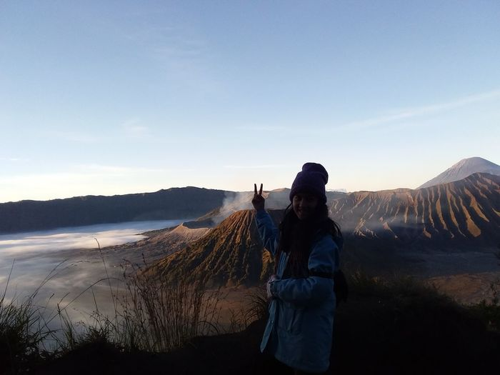 Woman gesturing peace sign while standing on volcanic landscape against sky