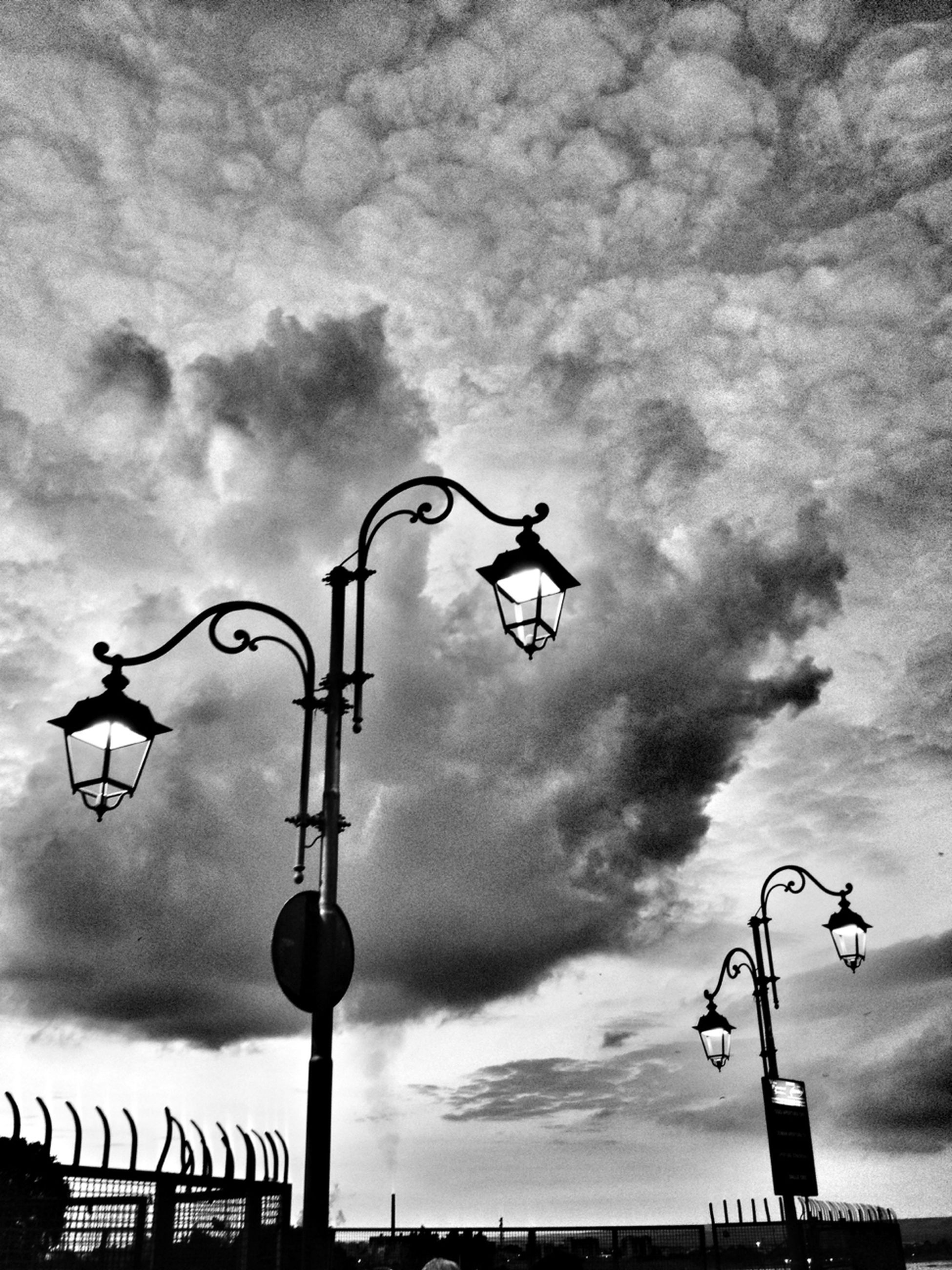 sky, cloud - sky, low angle view, cloudy, silhouette, overcast, cloud, street light, weather, dusk, lighting equipment, metal, communication, outdoors, pole, no people, animal representation, bicycle, day, text
