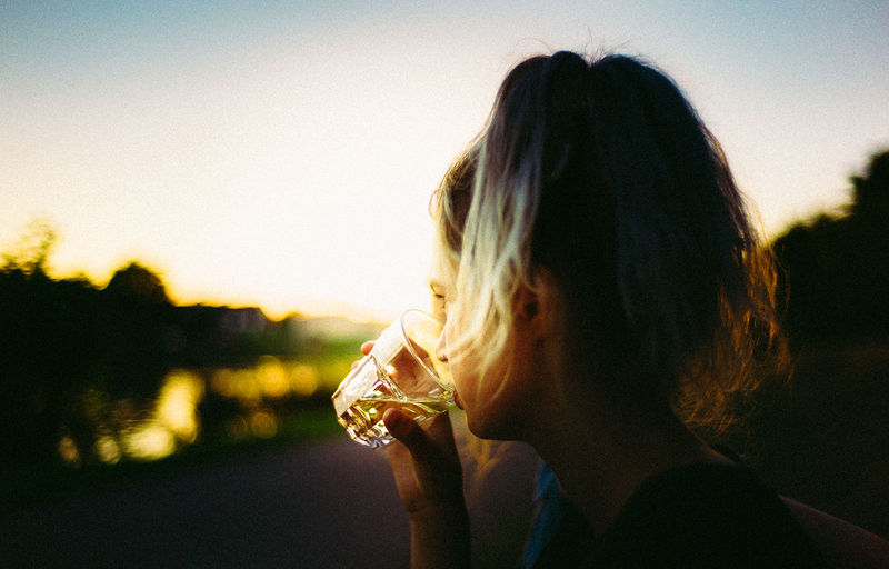 Close-Up Of Woman Drinking Whiskey Against Sky